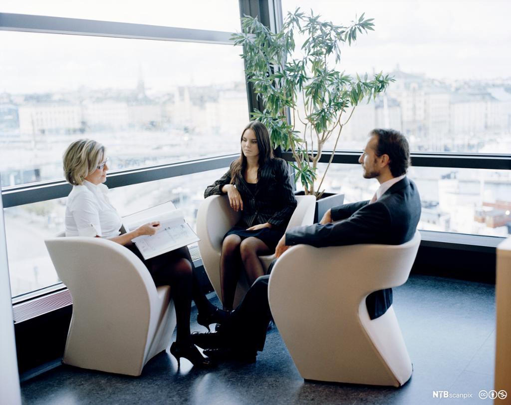 Tre personer sitter og snakker sammen i en kontorbygning med store glassvindu. Foto.