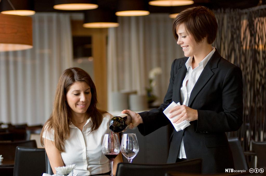 En servitør serverer vin til en gjest. Foto.