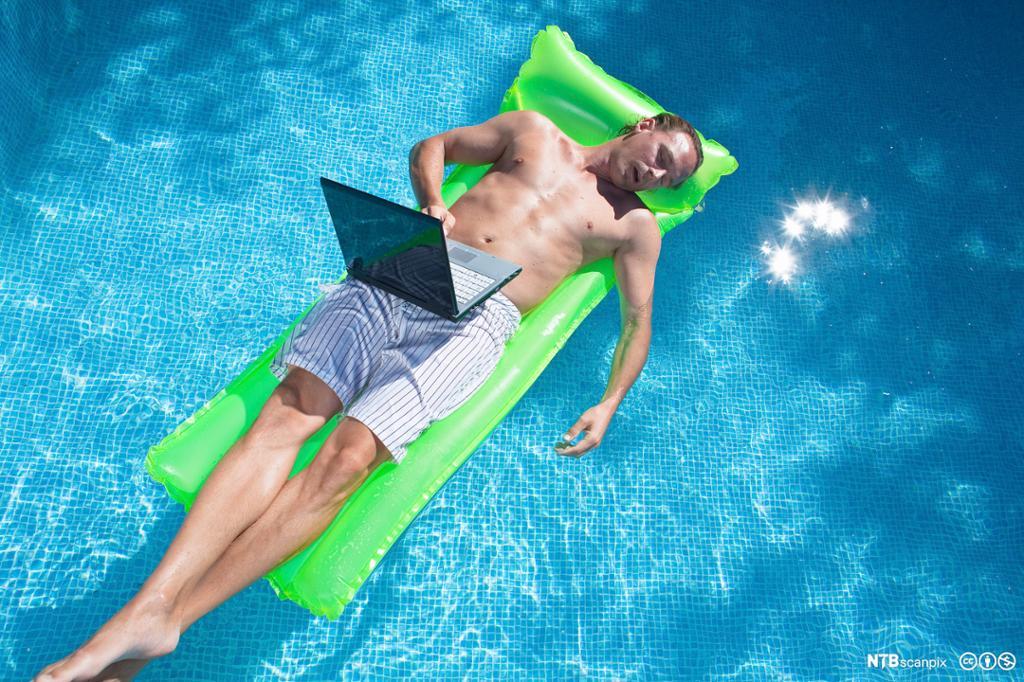 Mann ligger på en luftmadrass med laptop på fanget i et badebasseng og sover. Foto.