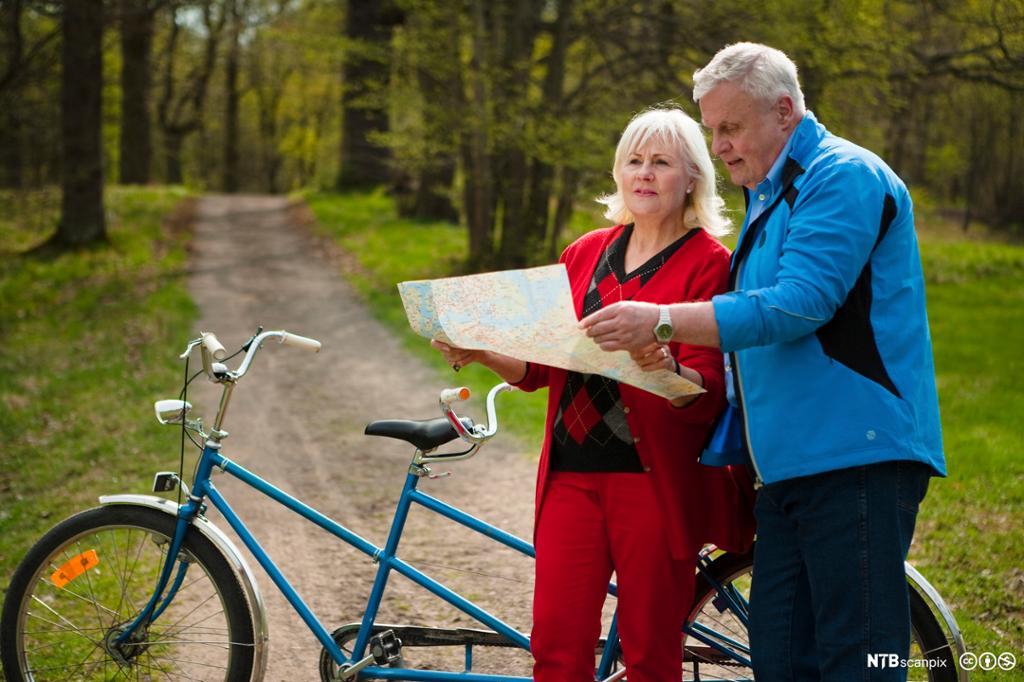 Eldre par med tandemsykkel studerer et kart. Foto.