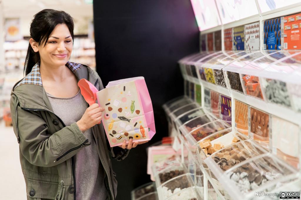 Kvinne kjøper smågodt i løs vekt. Foto.