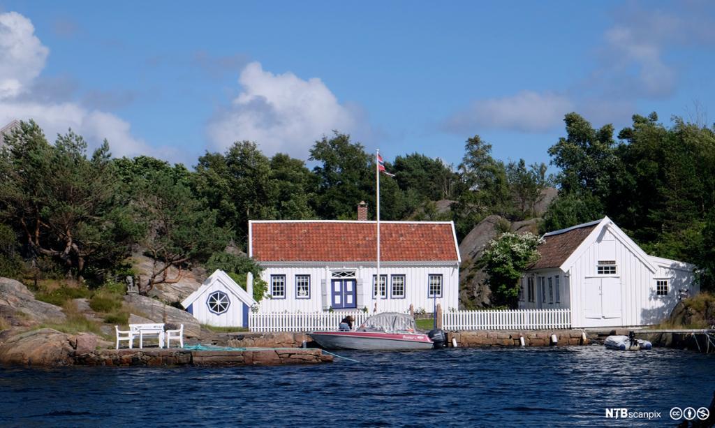 Hvitt sørlandshus med bå inngangsdør ved sjøen. Foto.