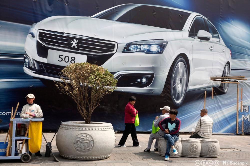 Mennesker passerer en reklamevegg for Peugeot på en åpen plass i Beiking. Foto.