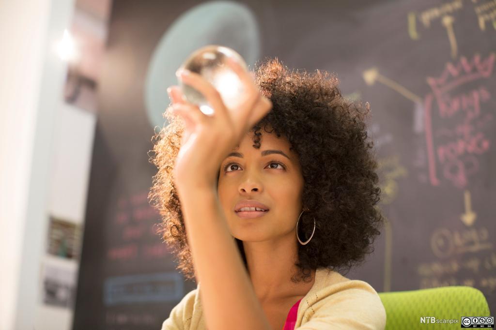 Kvinne ser inn i glasskule, i bakgrunnen ei tavle med tankekart skrevet med farget kritt. Foto.