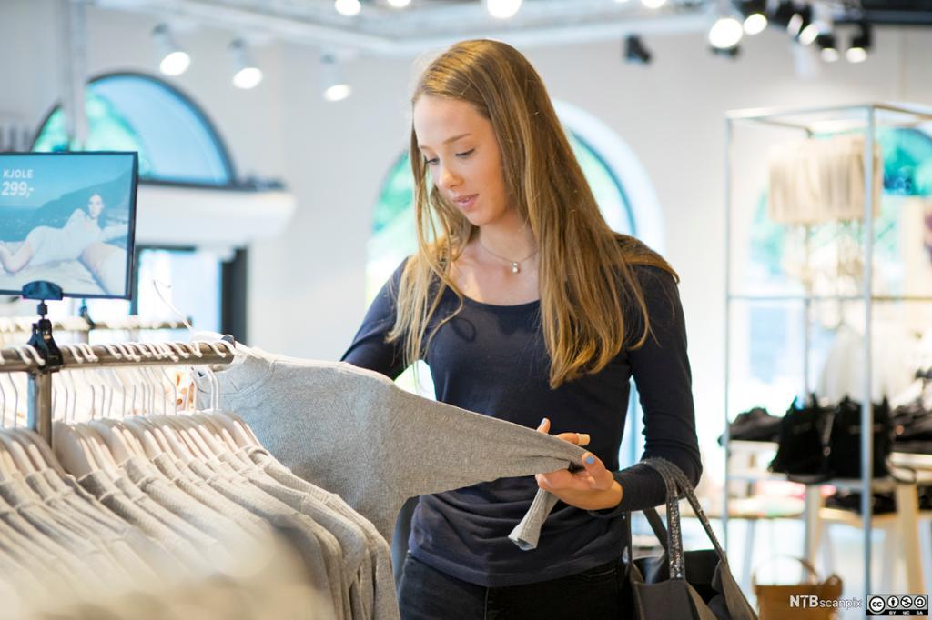 Jente ser på klær i en klesbutikke. Foto.