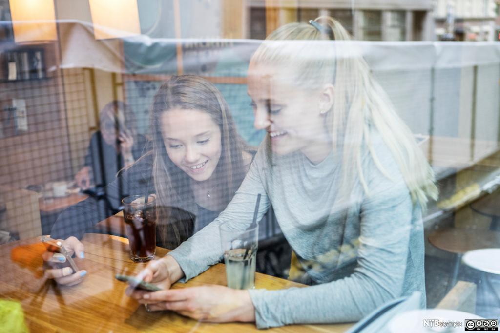 To unge kvinner med mobiltelefoner bak et vindu. Foto.