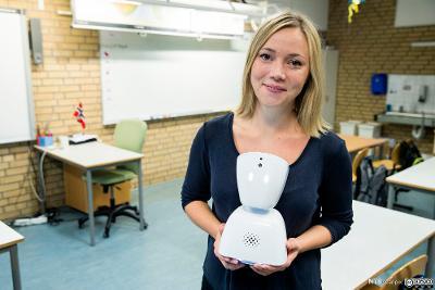 Ung kvinne holder klasseromsrobot i et klasserom. Foto.
