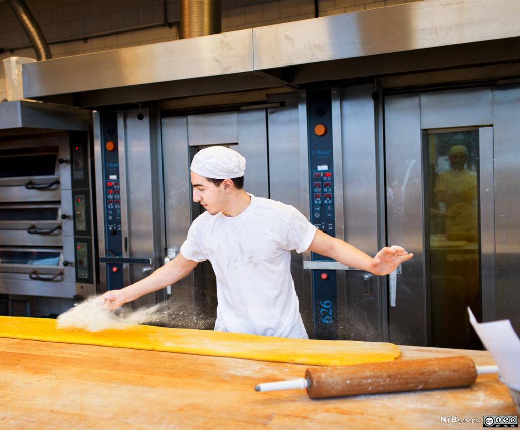 Bildet viser en baker som baker boller.