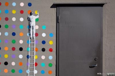 Veggmaleri som viser en mann som står på en stige og maler sirkler i mange farger på en grå vegg. Foto.