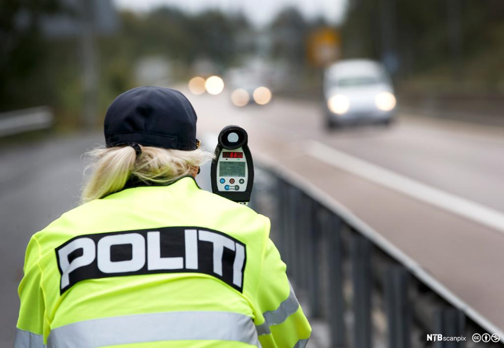 Bilde av en politimann som utfører trafikkontroll med lasermåler