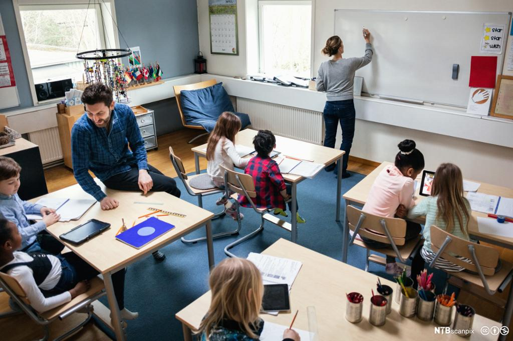 Oversiktsbilde fra et klasserom med to lærere og flere elever. Foto.