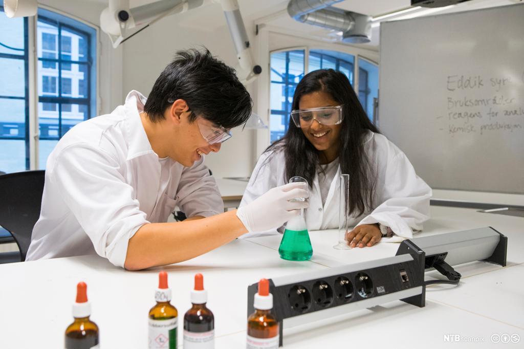 To ungdommer i hvite frakker i kjemilaboratorium. Foto.