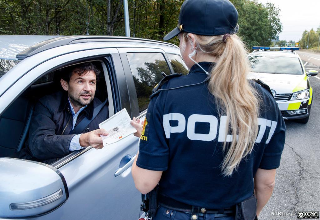 En kvinnelig politikonstabel sjekker vognkort og førerkort. Foto.