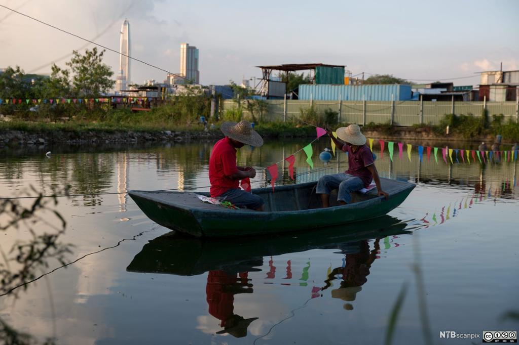 To fiskere i en liten båt utenfor Hong Kong. Foto.