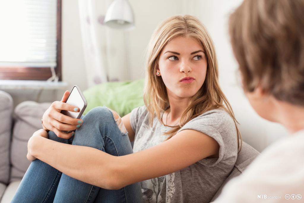 Jente i sofa i samtale med en kvinne. Foto.