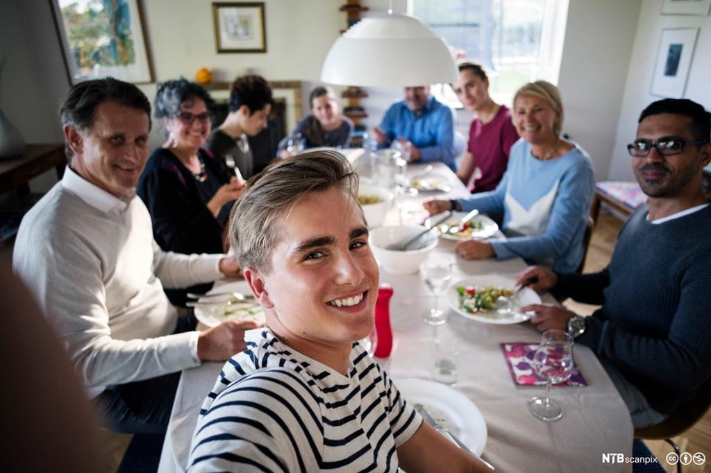 En tenåringsgutt sammen med familie og venner rundt et middagsbord. Foto.