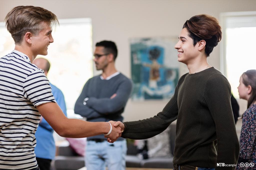 Smilende multietniske gutter håndhilser. Foto.