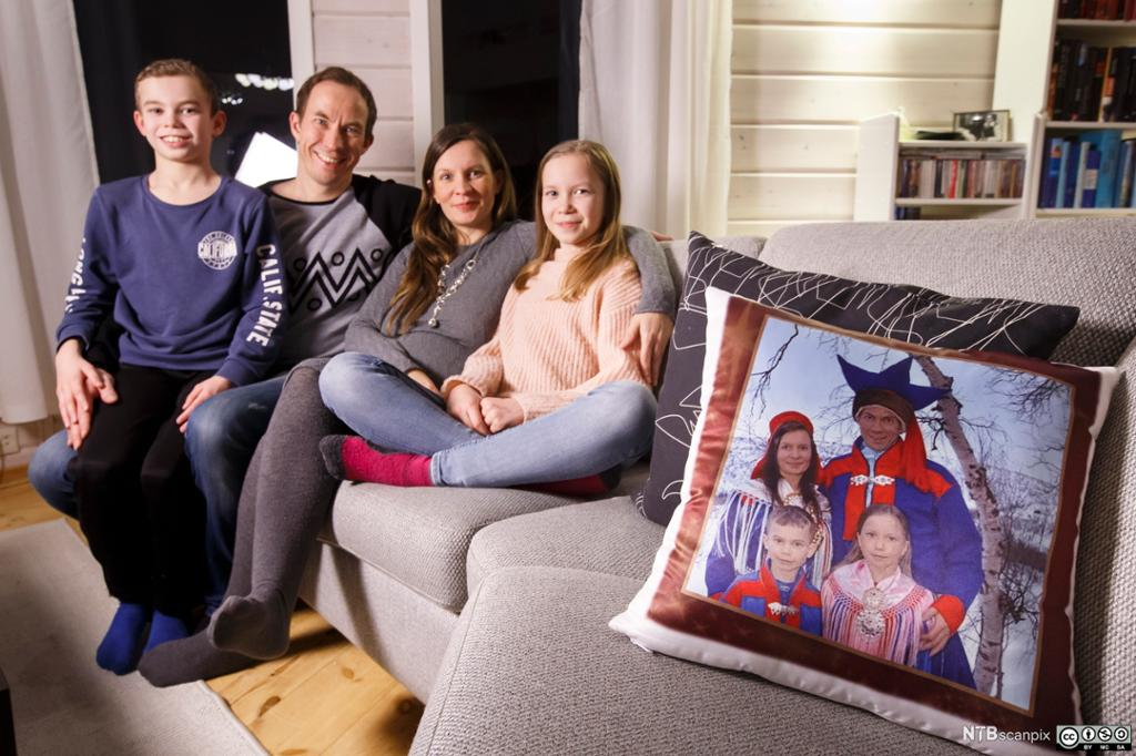 Familie i sofakroken med en pute som viser dem i samedrakter. Foto.