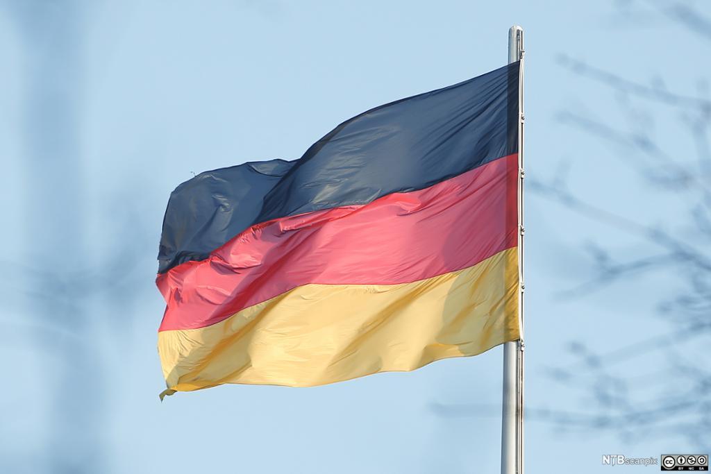 Tysk flagg som vaier i vinden. I bakgrunnen en lyseblå himmel med lette skyer. Foto.