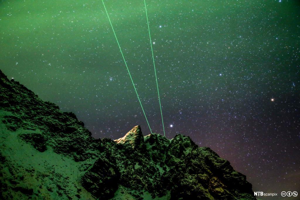 To grønne laserstråler fra fjelltopp med nordlys over nattehimmelen. Foto