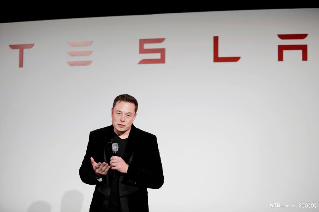 Elon musk prater under en Tesla-logo. Foto.