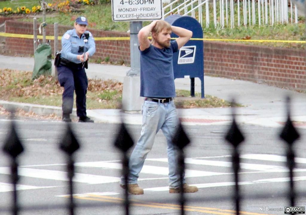 Mann med hendene over hodet overgir seg til politiet. Foto.