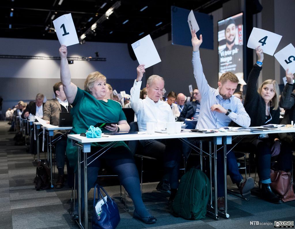 Sentrale høyrepolitikere holder stemmesedler i været. Foto.