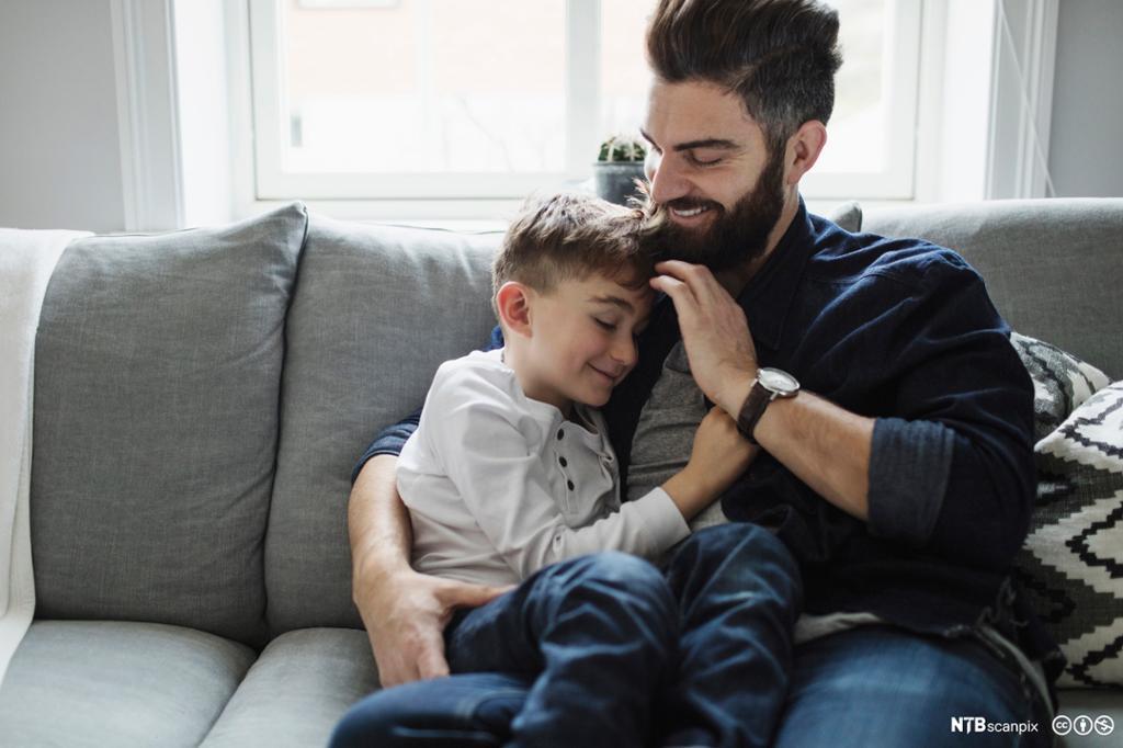 Et fotografi av far og sønn i en sofa.