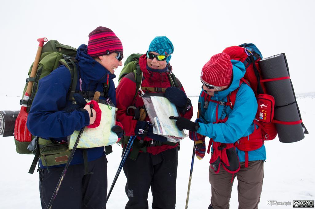 Tre kvinner på skitur i fjellet sjekker kartet. Foto.