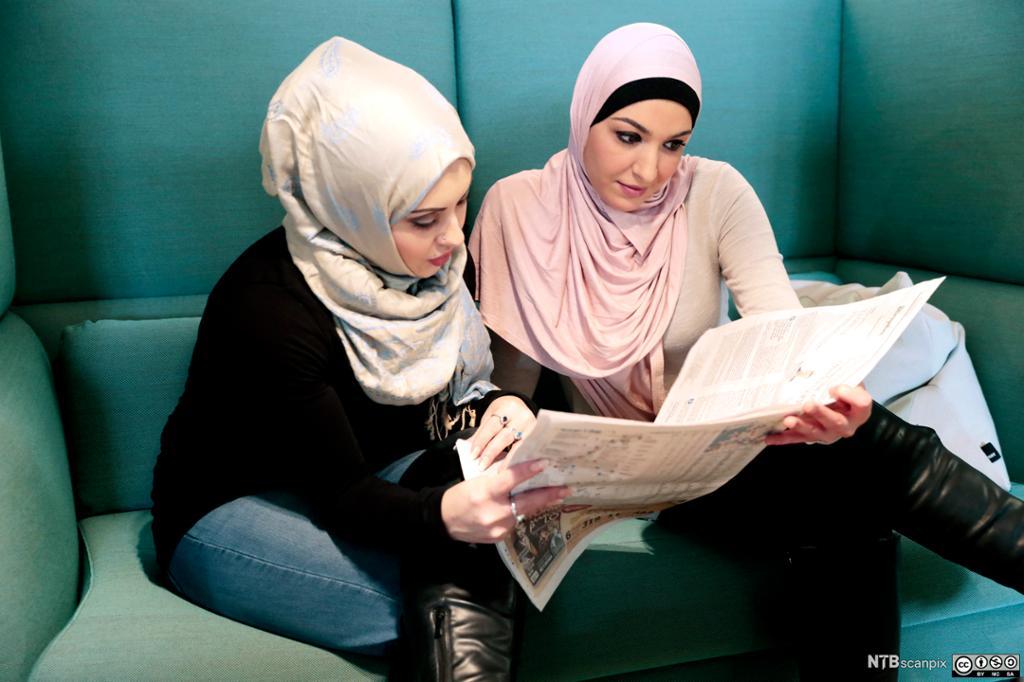 Jo unge damer med hidjab leser avis. Foto.