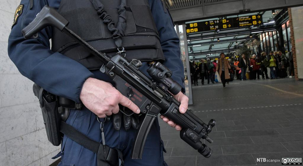 Politimann med maskingevær. Foto.