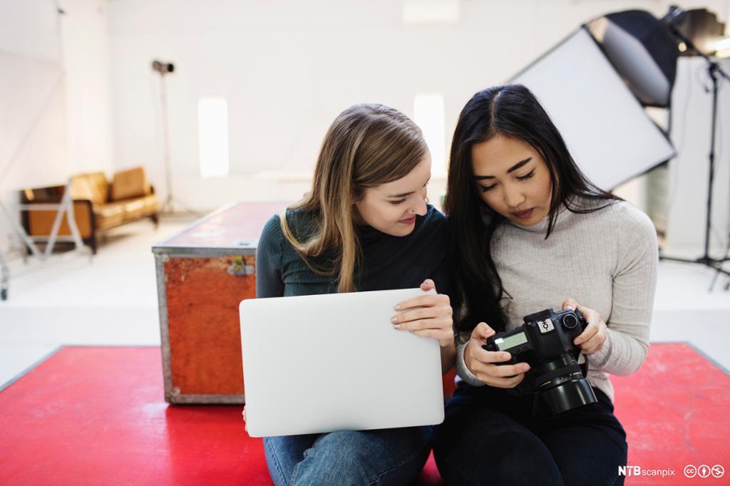 To bloggere ser på bilder på digitalt kamera. Foto.