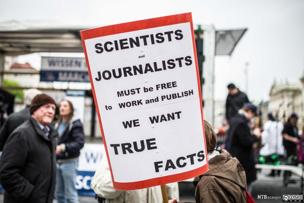 Plakat i demonstrasjonstog som krever sanne fakta i journalistikk og vitenskap. Foto.