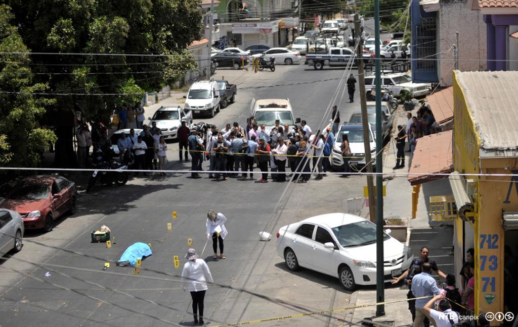 Tildekket lik liggende i gata. Politi og tilskuere tilstede. Foto.
