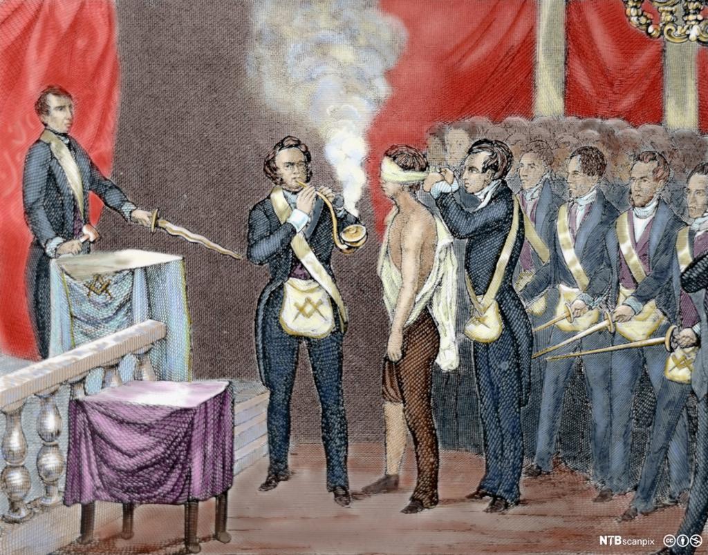 Til venstre står en mann på et podium ved en talerstol med et sverd og en klubbe i hendene. I sentrum står en mann og røyker på en stor pipe. En annen mann er halvveis påkledd og får et bind satt for øynene. Til høyre står en forsamling av menn. Alle har lik uniform. Illustrasjon.