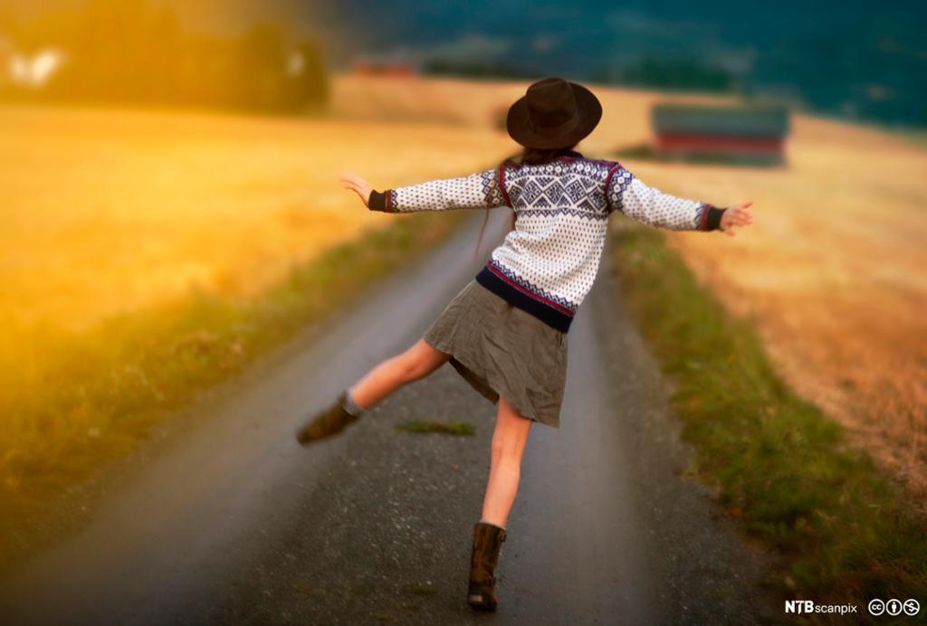 Jente som danser langs en landevei. Foto.