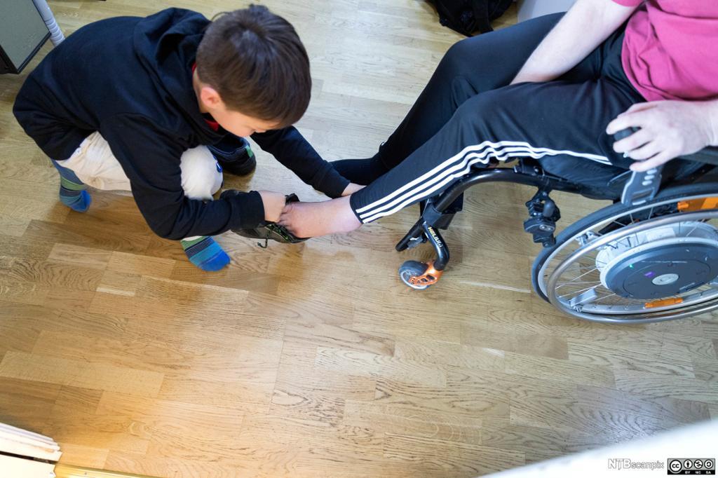 Gut hjelper mann i rullestol med å ta på sko. Foto.