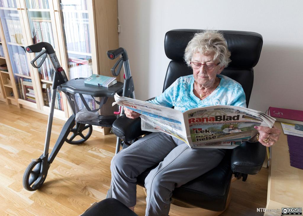 Eldre dame med gåstol leser papiravis. Foto.