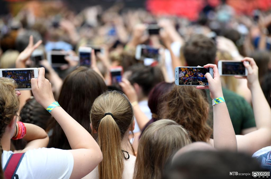 Mange ungdommer som filmer med mobiltelefonene. Foto.