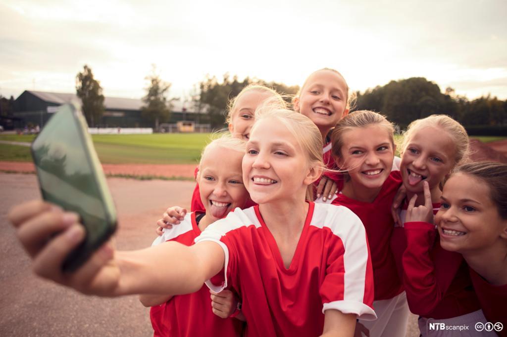 Blide fotballjenter tar en selfie sammen. Foto.