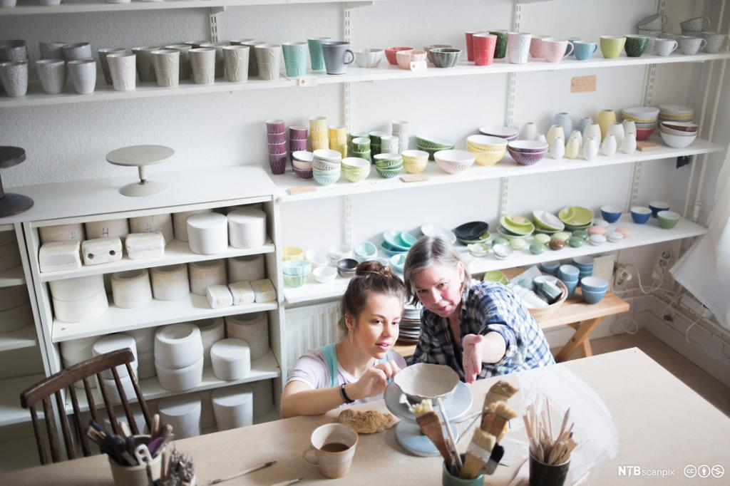 To keramikere ser på keramikk. Foto.