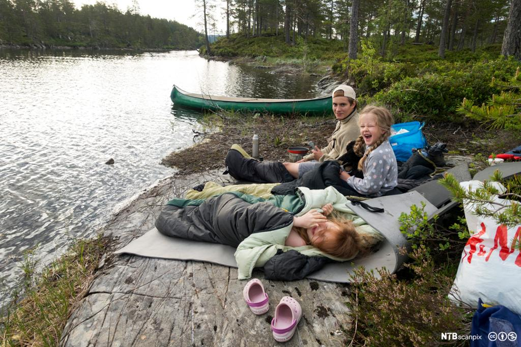 Tre barn overnatter ved vann og har kano. Foto.
