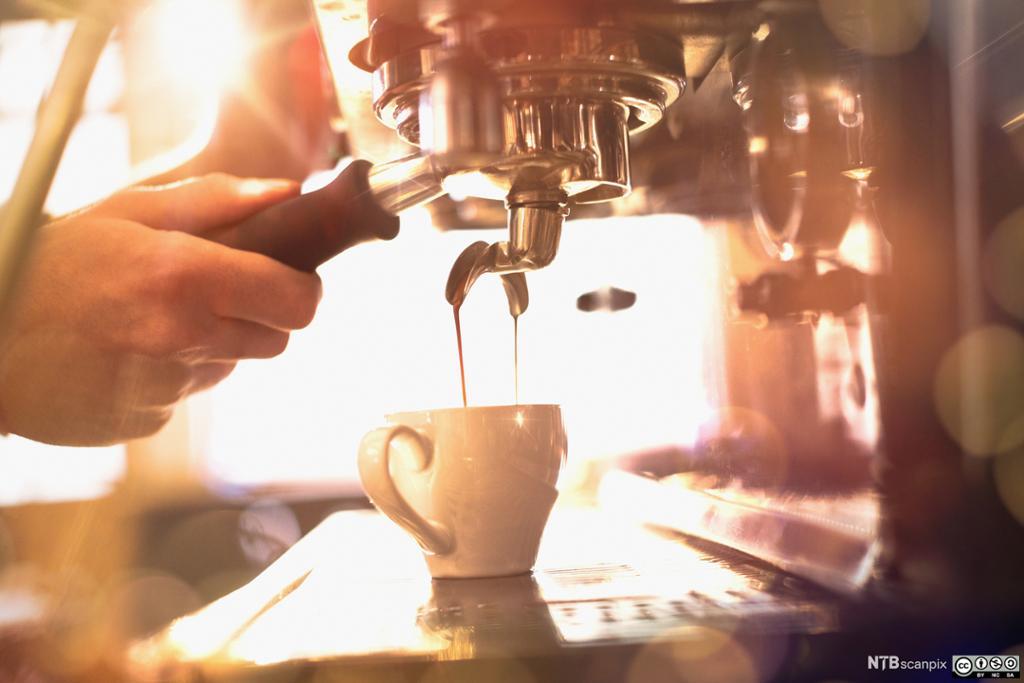 Espresso fylles i ein kopp. Foto.