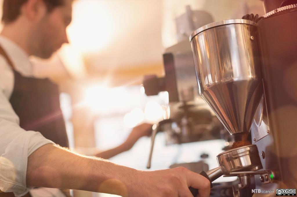 En mann kverner kaffe i en espressomaskin. Foto.