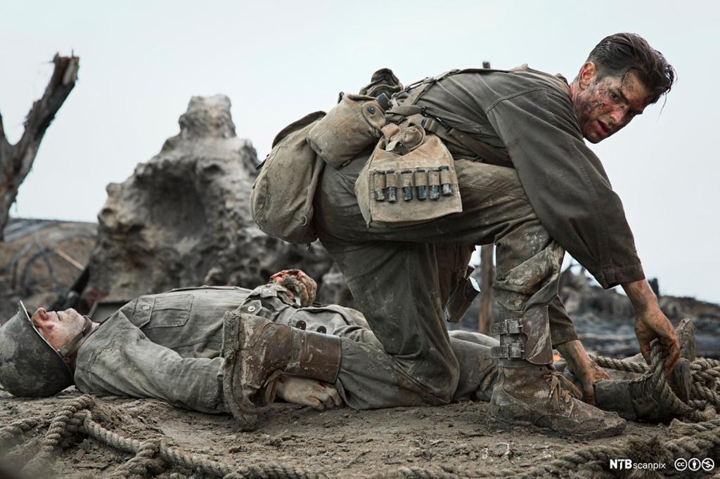 Soldat sitter på huk på en slagmark. Bak ham ligger en død eller skadet soldat. Foto.