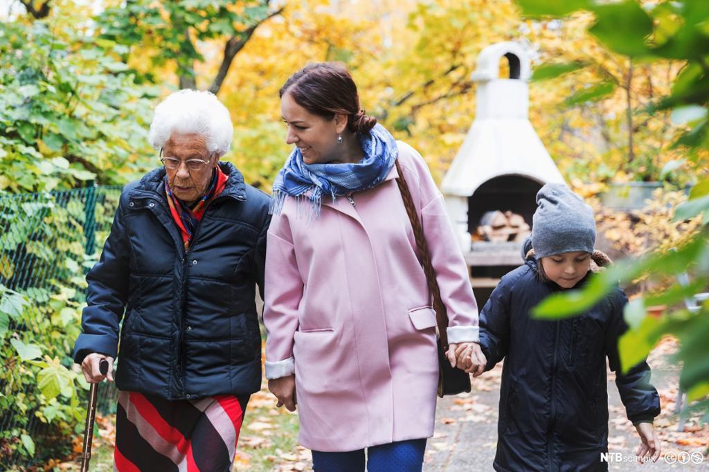 Et fotografi av en eldre kvinne med sin datter og oldebarn.