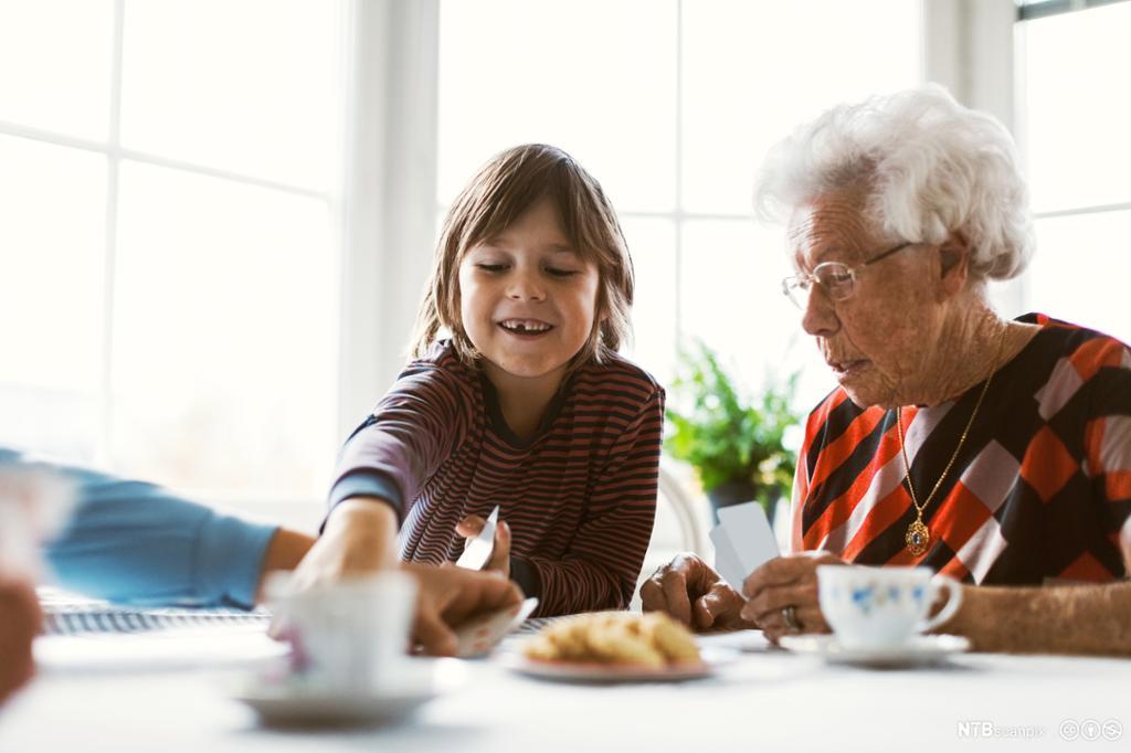 Et fotografi av en ung gutt og gammel dame som spiller kort ved et kjøkkenbord.