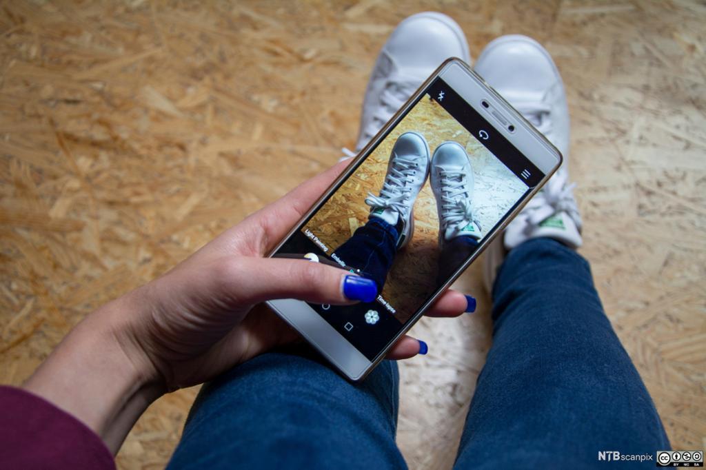 En ung jente tar bilde av joggeskoene sine med mobiltelefon. Foto.