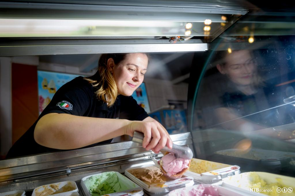 Ung kvinne i isbar fyller en kjeks med jordbæris. Hun smiler. Foto.