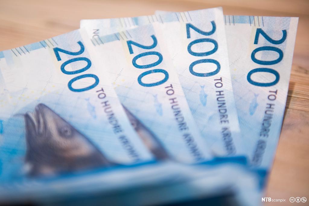 En hånd som holder pengesedler, med mynter på bord i bakgrunnen. Foto.